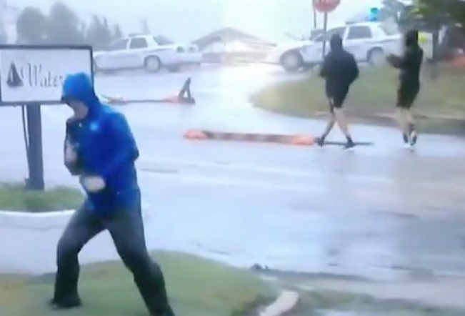 Photo of Hilarious fake news: Weather Channel reporter fakes hurricane-force winds while two guys casually stroll down the street behind him, wearing shorts